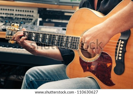 left-handed man playing guitar, close-up - stock photo