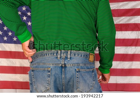 Left-handed shooter with hand on gun standing in front of US flag - stock photo