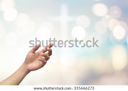 left hands of man  praying on blurred bright color pastel background with bokeh christmas lights:hand palm up open receiving power from god.religion abstract concept.faith and strength conceptual. - stock photo