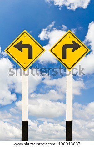 Left turn and right turn road signpost on cloudy sky background - stock photo