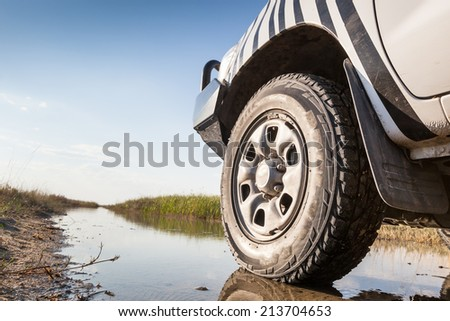 left wheel of a white 4x4 car on a wet trail in the marsh of Nata bird sanctuary, Botswana, Africa - stock photo