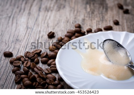 Leftovers of coffee foam on saucer with spoon placed on wooden background with coffee beans. Frontview with copy-space. - stock photo