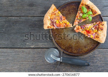 leftovers of homemade vegetarian pizza from above on wooden table - stock photo
