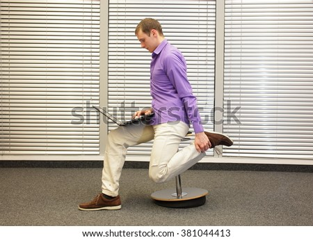 leg exercise during office work -  man sitting on pneumatic stool, working with laptop in his office - stock photo