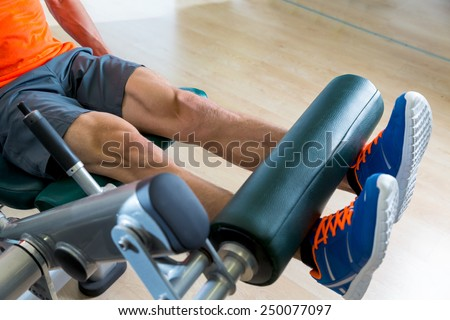 Leg extension exercise man at gym indoor workout - stock photo