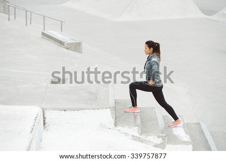 Leg lunges exercise on stairs. Fitness woman working out on urban park. - stock photo