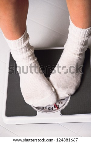 Leg of a woman standing on a bathroom scale - stock photo