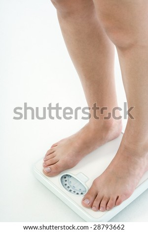 Leg of Caucasian female with untidy nails standing on bathroom scales, checking her weight over 220 lbs - stock photo
