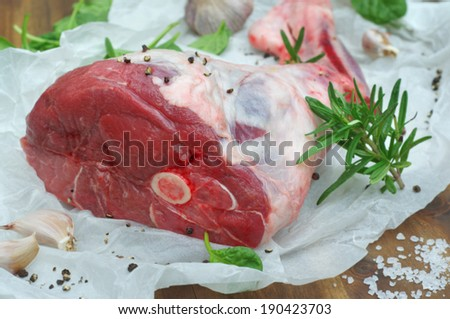 leg of lamb with salt, garlic, rosemary and baby spinach on a wooden background - stock photo