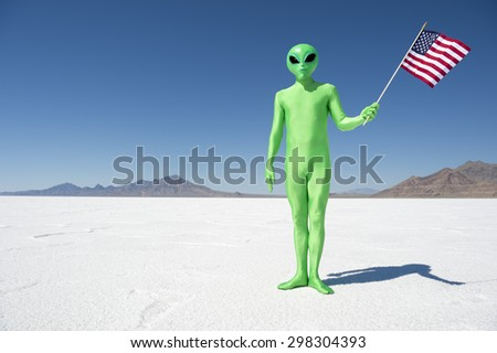 Legal (or illegal) alien making a patriotic immigration statement holding an American flag on dramatic lunar landscape - stock photo