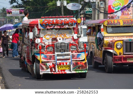 LEGAZPI, PHILIPPINES - MARCH 18, 2014: Jeepneys passing, Filipino inexpensive bus service. Jeepneys are the most popular means of public transportation in the Philippines. - stock photo