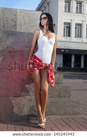 leggy beautiful lady standing on sidewalk of city - stock photo