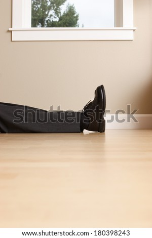 Legs and feet of business man laying passed out on floor - stock photo