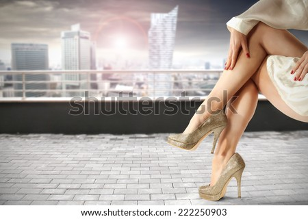 legs and modern city landscape  - stock photo