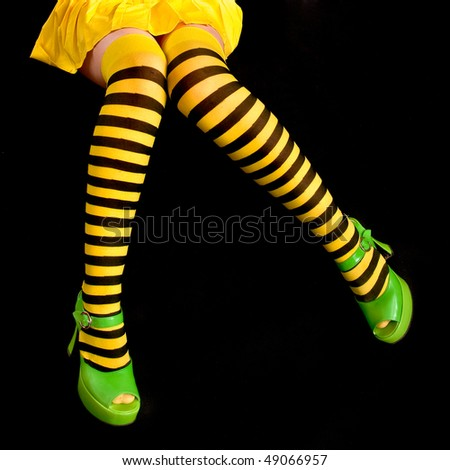 legs clothed in black and yellow striped tights - stock photo