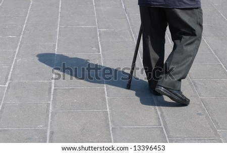Legs detail of a senior man walking with help of a walking stick. - stock photo