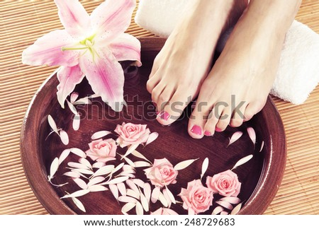 Legs, flowers, petals and ceramic bowl. Spa, recreation and skin care concept.  - stock photo
