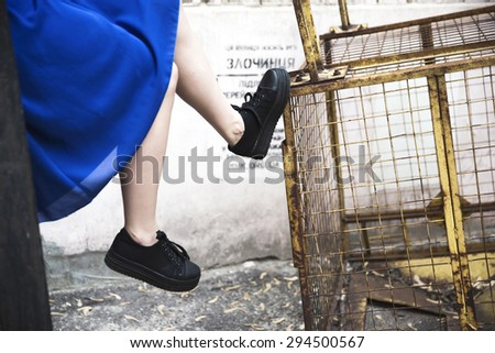 Legs in sneakers of young beautiful brunette woman in casual clothes on industrial  background; outdoor - stock photo