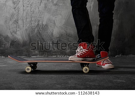 Legs in sneakers on a skateboard - stock photo