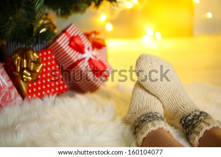 Legs in socks near Christmas tree on carped - stock photo