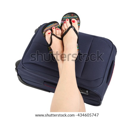 Legs lying on the blue suitcase - stock photo