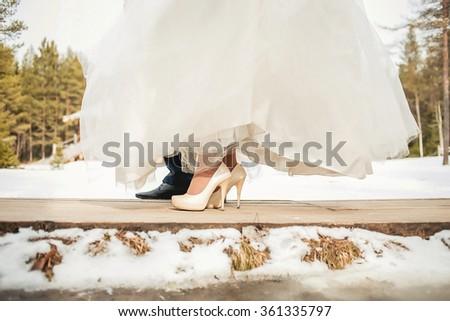 Legs newlyweds on wooden bridge  in winter wedding day - stock photo