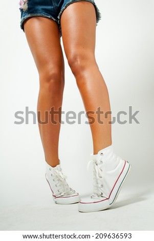 legs of a beautiful girl in sneakers - stock photo