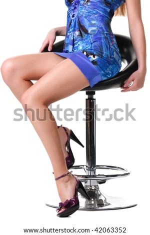 Legs of a beautiful woman sitting on a chair. Isolated over white background . - stock photo