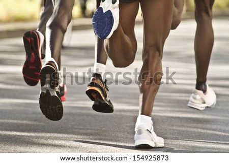 Legs of a group street marathon runners - stock photo