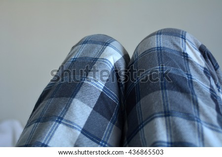 Legs of a man wearing pyjamas lie in bed. Laziness concept - stock photo
