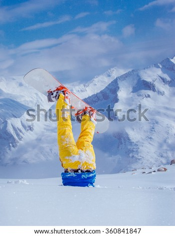 Legs of a snowboarder stuck in deep snow upside down, mountains at the background - stock photo