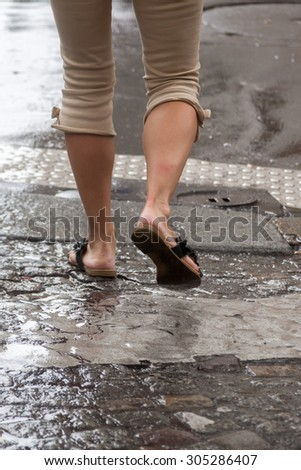 legs of a woman crossing a rainy street - stock photo