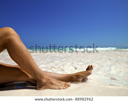 legs of a woman on the beach - stock photo
