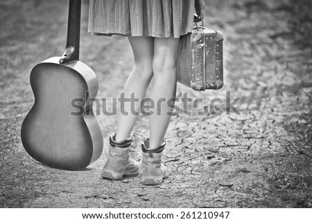 Legs of a woman traveler with suitcase and guitar standing on rural road. black and white, toned vintage image, vignette,  copy space - stock photo