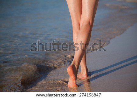 Legs of a young woman walking along the seacoast - stock photo