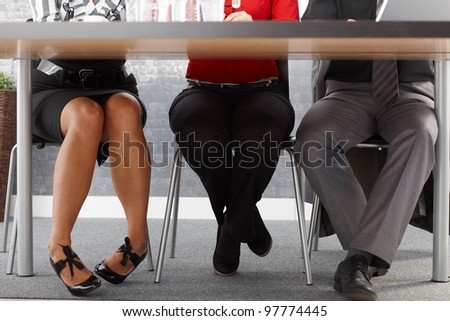 Legs of businesspeople at meeting, sitting together at meeting table in office. - stock photo