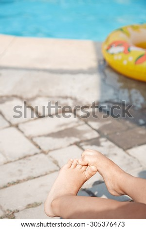 Legs of child at the swimming pool. Life ring on the background - stock photo