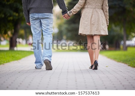 Legs of couple walking in park - stock photo