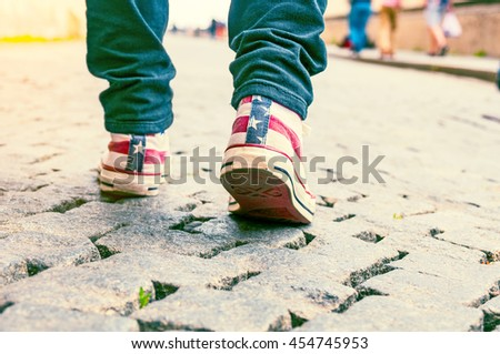 Legs of girl in sneakers on pavement. Toned image - stock photo