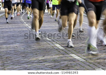 Legs of marathon runners in dynamic composition, legs being blurred because of low shutter speed - stock photo