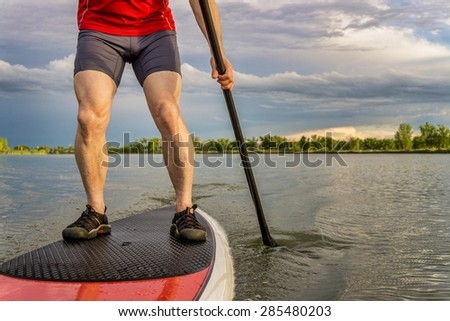 legs of muscular male paddler on a stand up paddleboard - a calm lake in summer - stock photo