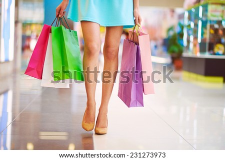Legs of shopaholic wearing blue dress while carrying several paperbags - stock photo