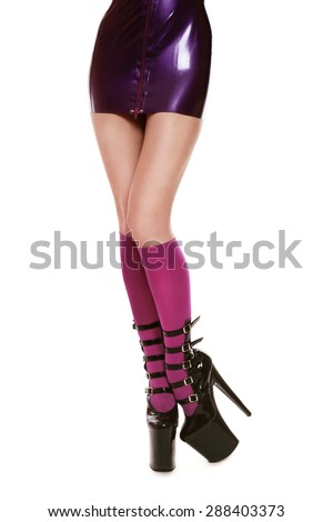Legs of slim sexy woman in latex dress, stockings and fancy stilettos over white background - stock photo
