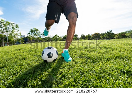 Legs of soccer player kicking the ball - stock photo