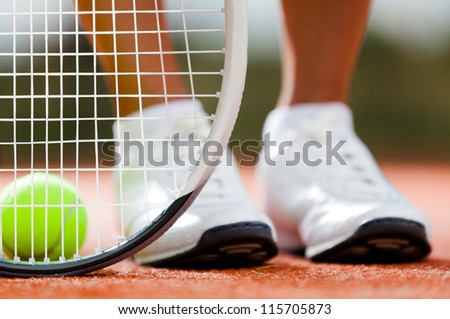 Legs of sportive girl near the tennis racquet and balls - stock photo