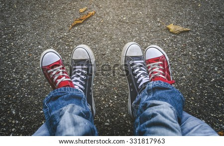 Legs of the child in gym shoes and feet of an adult shoes - stock photo