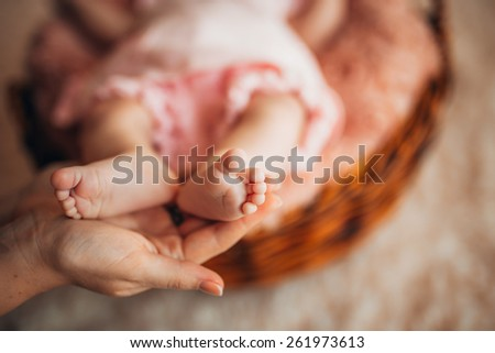 Legs of the child in my mother's arms. Child's feet in mother - stock photo