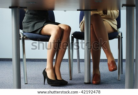Legs of two businesswomen under the meeting room table - stock photo