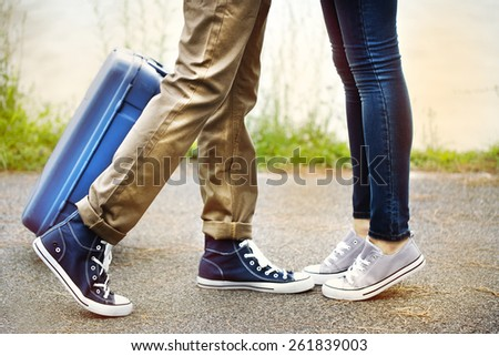 legs of two lovers meet with suitcase - stock photo