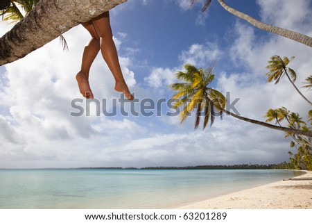 Legs of women seat on palm tree in a white sand beach of a paradise island - stock photo